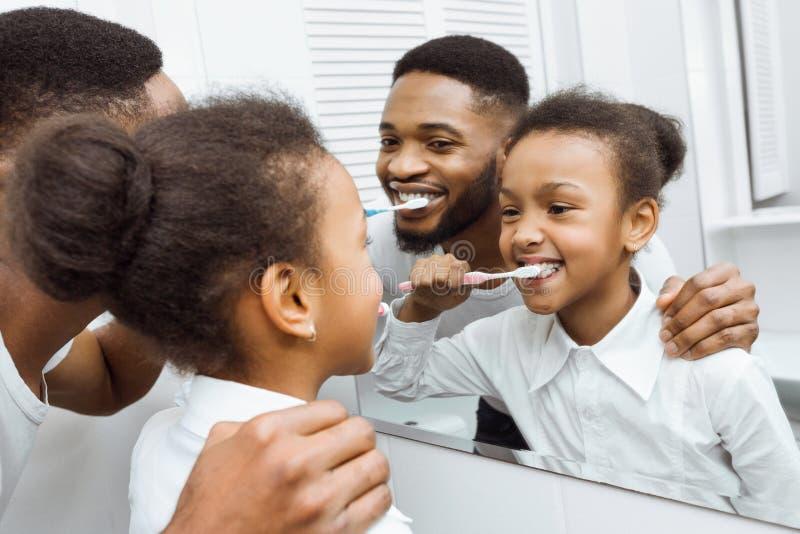 非裔美国人的与爸爸一起的女孩掠过的牙 免版税库存图片