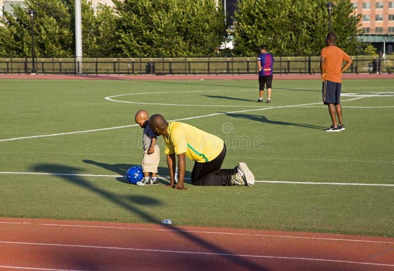 非裔美国人的人,教男孩踢足球洋基体育场轨道布朗克斯NY 库存图片