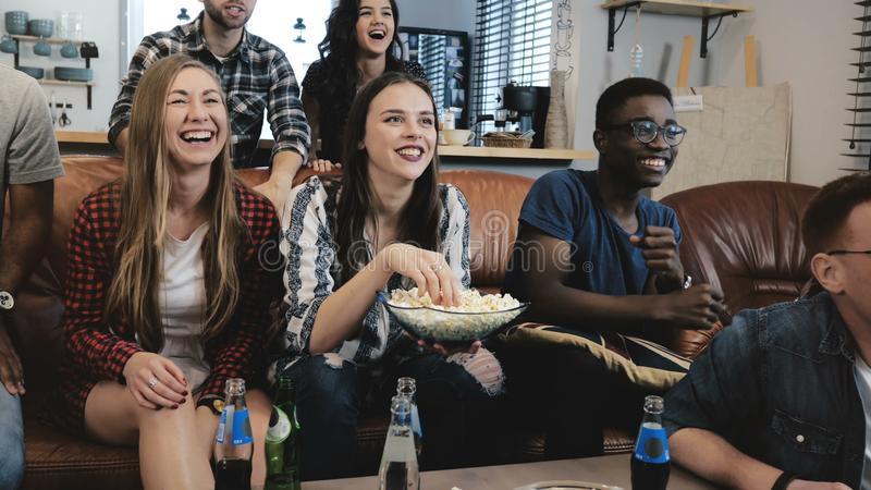 非裔美国人的体育迷在家庆祝胜利 热情的在电视的支持者呼喊观看的比赛 4k慢动作 免版税库存图片