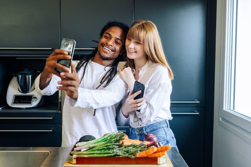 非裔美国人的做一selfie的男孩和白女孩在厨房里 库存图片