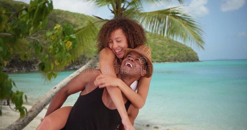 非裔美国人的千福年的夫妇由海滩互相给肩扛乘驾 免版税图库摄影