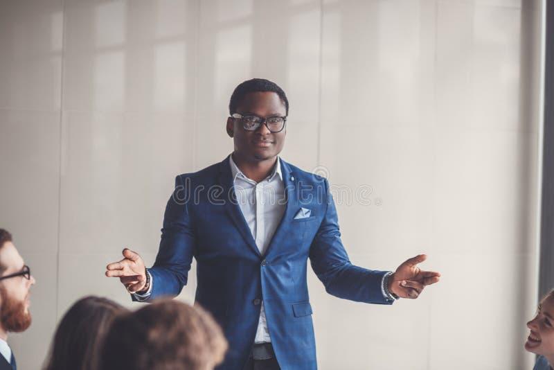 非裔美国人的商业领袖的图象在工作环境里的看照相机 库存照片