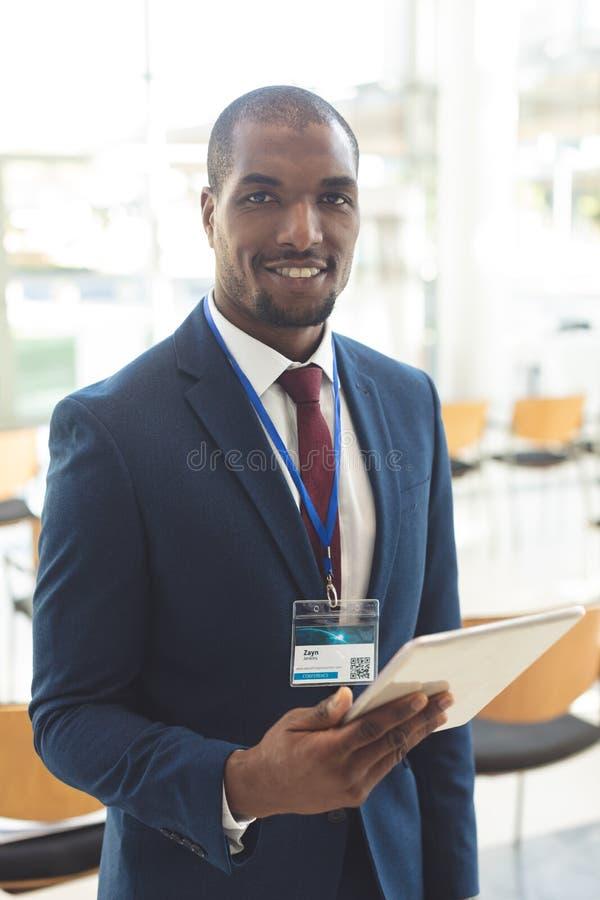 非裔美国人的商人身分在有片剂的会议室 图库摄影
