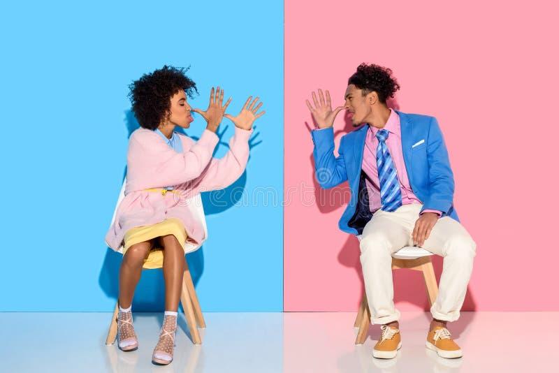 非裔美国人的夫妇互相做鬼脸,当坐椅子反对桃红色和蓝色时 库存图片