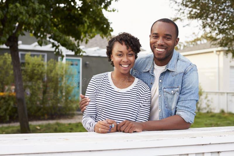非裔美国人的夫妇看对照相机他们的房子外 库存图片