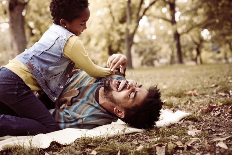 非裔美国人的女儿和父亲在草甸 免版税库存照片
