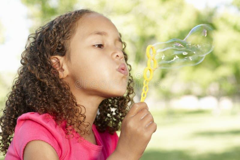 年轻非裔美国人的女孩吹的泡影在公园 免版税库存照片