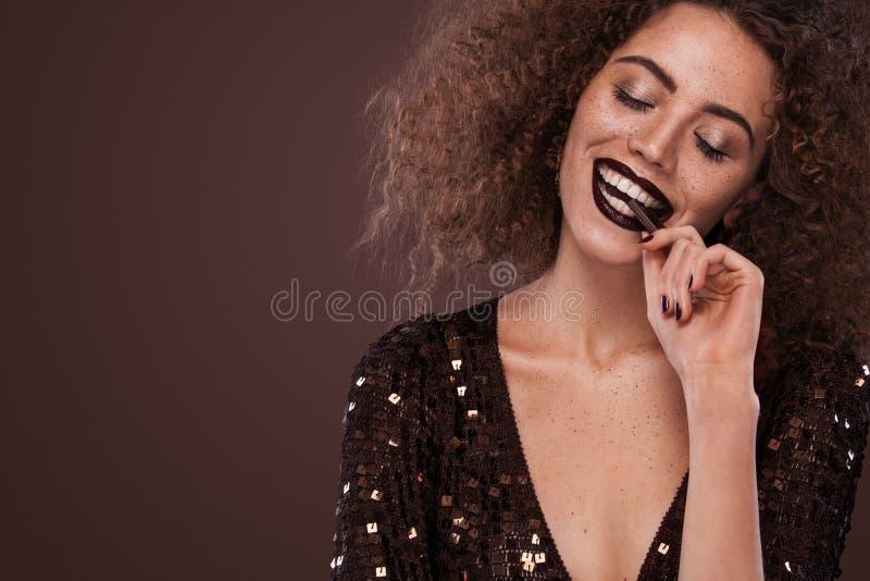 年轻非裔美国人的女孩秀丽画象有非洲的发型和巧克力的 摆在棕色背景的女孩 库存图片