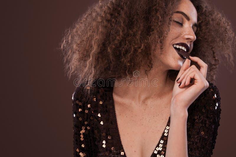 年轻非裔美国人的女孩秀丽画象有非洲的发型和巧克力的 摆在棕色背景的女孩 免版税库存照片