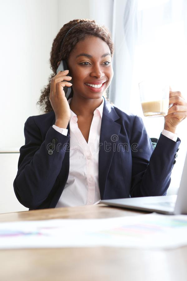非裔美国人的女实业家在打电话的办公室 免版税库存照片