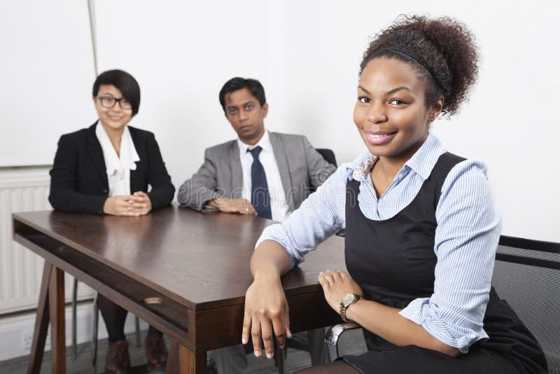 非裔美国人的女性画象有同事的在书桌的背景中在办公室 免版税库存照片