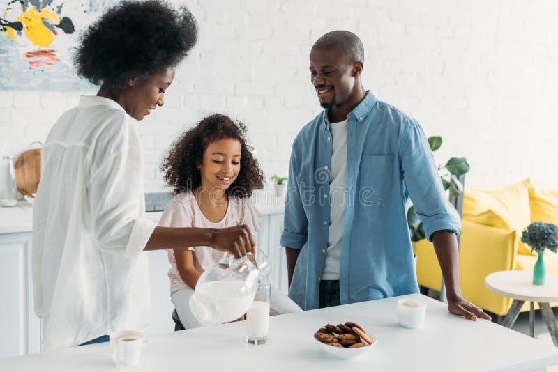非裔美国人的妇女倾吐的牛奶到与近家庭的玻璃里在厨房里 库存图片