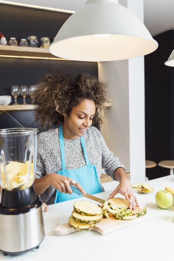 年轻非裔美国人的妇女切口果子在厨房里 图库摄影