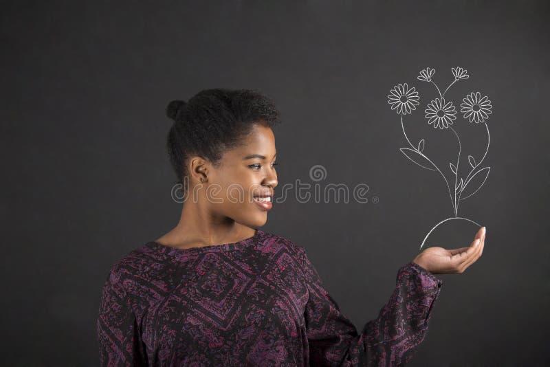 非裔美国人的妇女在她的手上的拿着一朵生长花 免版税库存照片