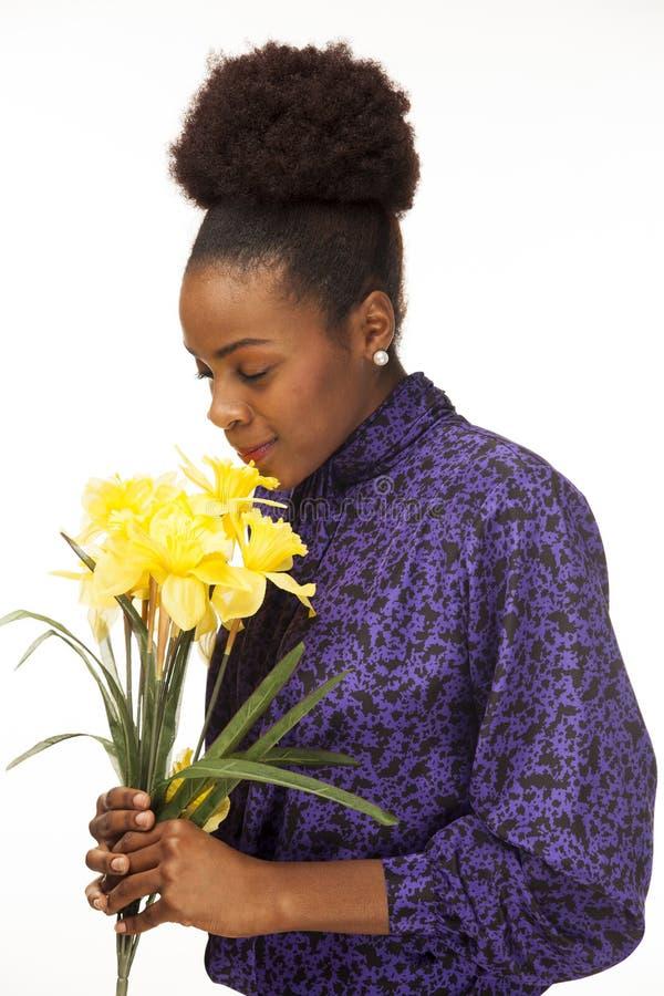 非裔美国人的妇女微笑,当嗅到鲜花时 库存照片