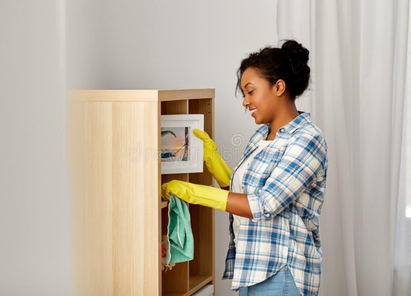非裔美国人的妇女打扫灰尘和清洗的家 免版税库存图片