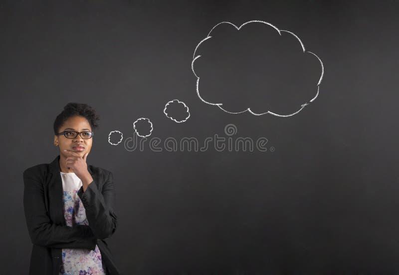 非裔美国人的妇女用在下巴想法的想法泡影的手在黑板背景 免版税库存照片