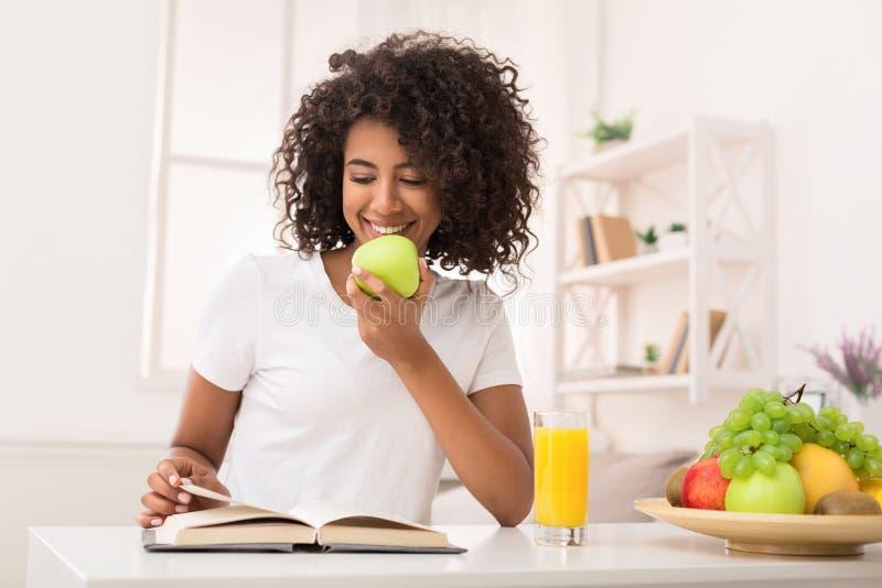 非裔美国人的妇女阅读书和吃苹果 库存图片