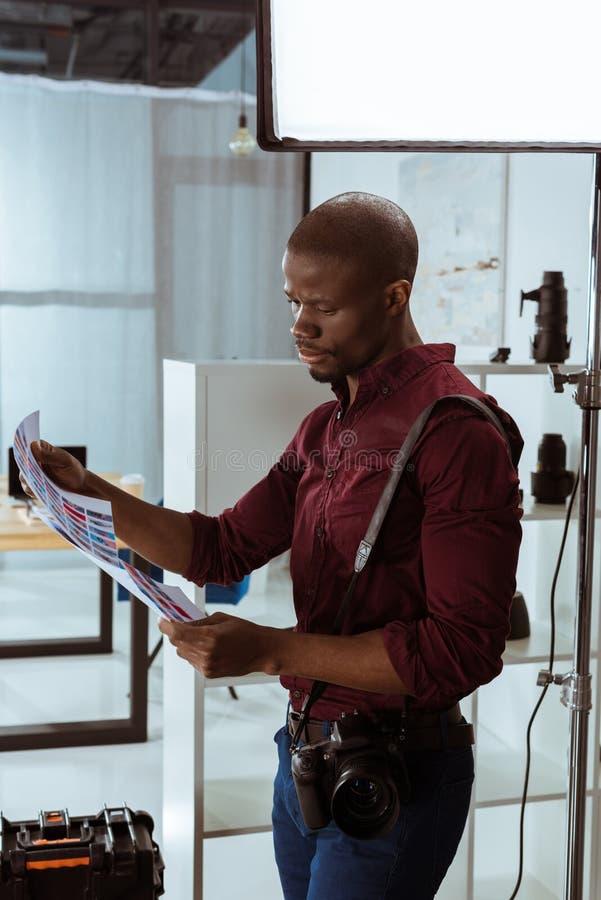 非裔美国人的摄影师侧视图有photoshoot例子的在手上 免版税库存图片