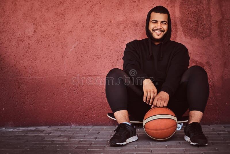 非裔美国人的有胡子的人在一黑有冠乌鸦穿戴了并且炫耀短裤坐与篮球的一个滑板和 库存图片