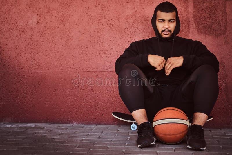 非裔美国人的有胡子的人在一黑有冠乌鸦穿戴了并且炫耀短裤坐与篮球的一个滑板和 免版税库存图片