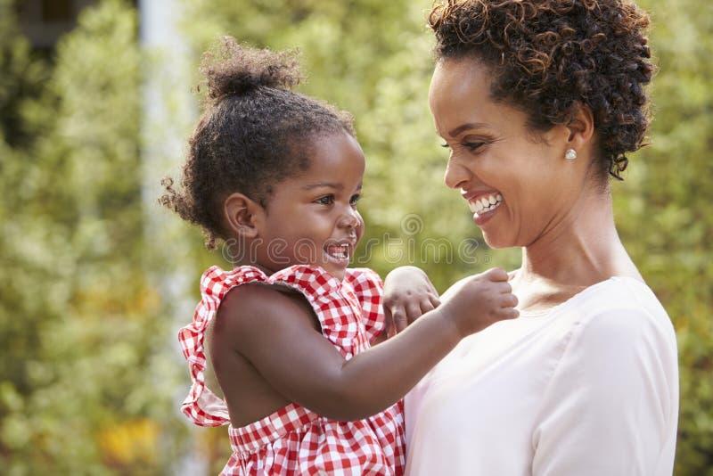 年轻非裔美国人的母亲在庭院里拿着小女儿 免版税库存照片