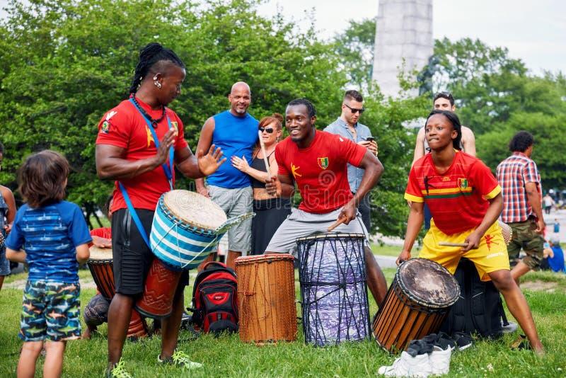 非裔美国人的演奏djembe和dunun鼓的男性和女性打击乐演奏者在Tam Tams节日在皇家山公园 免版税库存照片