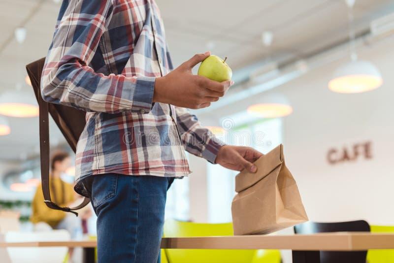 非裔美国人的男小学生播种的射击有苹果和午餐袋子的在学校食堂 库存照片