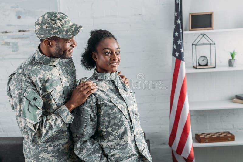 非裔美国人的男性士兵拥抱的妇女 免版税库存照片