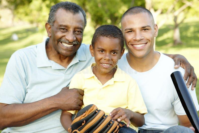 非裔美国人的祖父、打棒球的父亲和儿子在公园 免版税库存图片