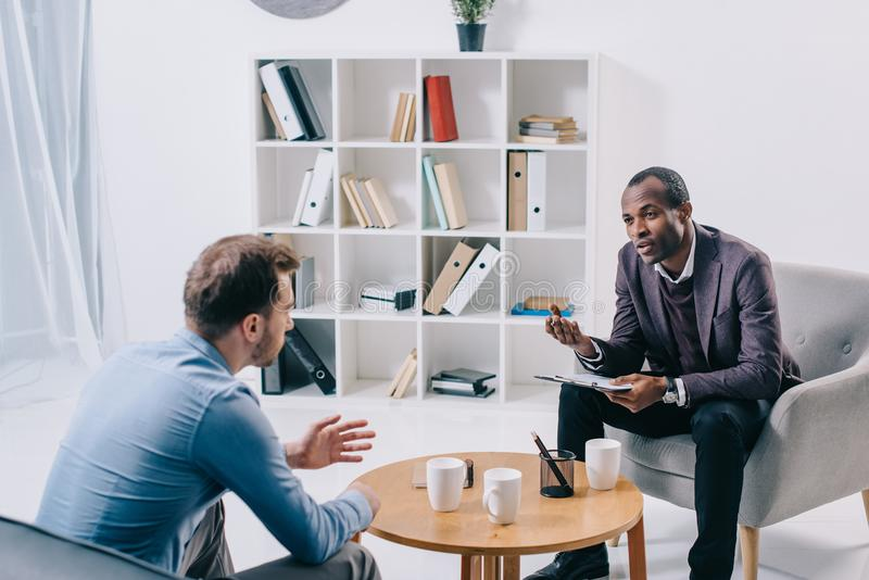 非裔美国人的精神病医生谈话与年轻男性 免版税库存照片
