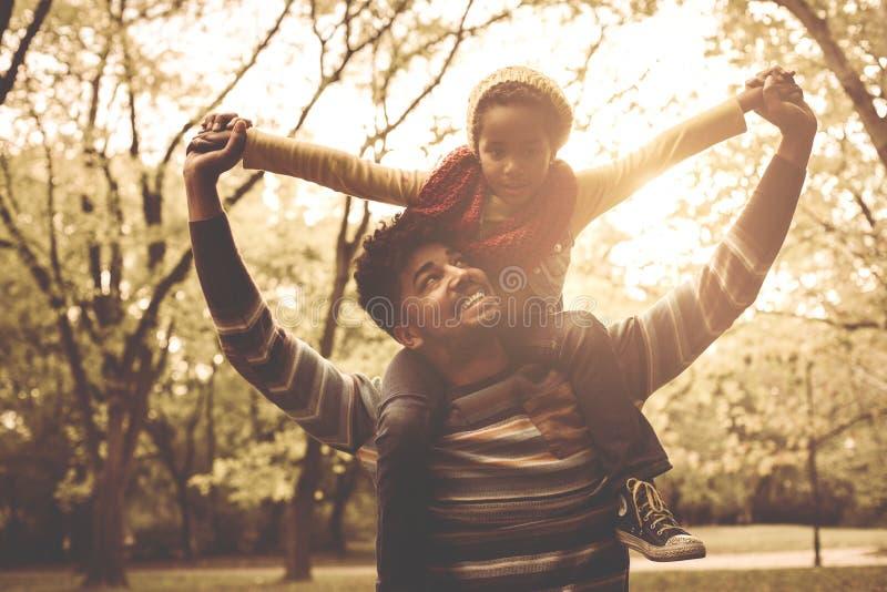 非裔美国人的肩膀的父亲运载的女儿 免版税库存照片