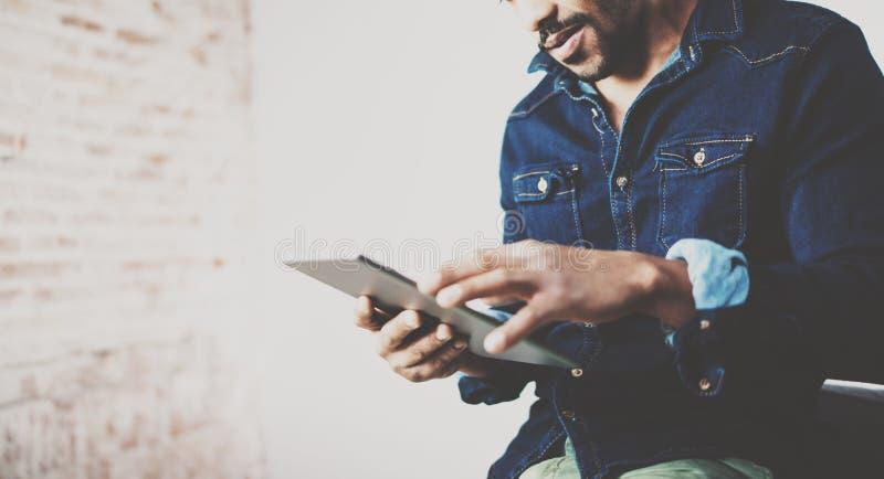 非裔美国人的自由职业者触摸屏数字式片剂播种的射击,当在家时工作在新的项目 投反对票 免版税库存图片