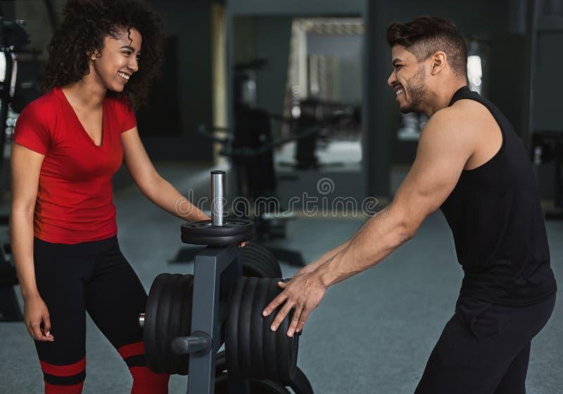 非裔美国人的运动员女孩谈话与在健身房的教练员 图库摄影