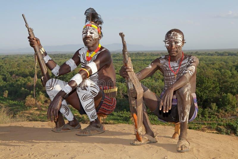 韩国人体村庄中的姑娘_karo族群的非洲人与部族人体彩绘的有攻击步枪在karo村庄, omo河谷