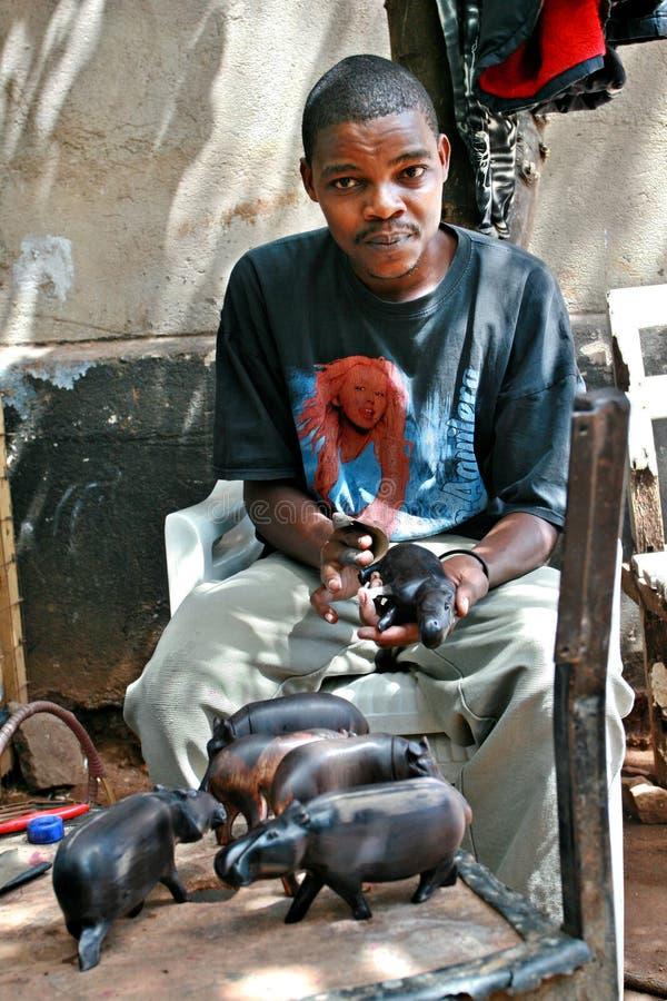黑非洲人木雕刻师运作的艺术车间 免版税库存图片