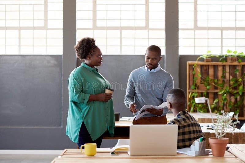非洲办公室同事一起谈论文书工作在办公室 免版税库存照片