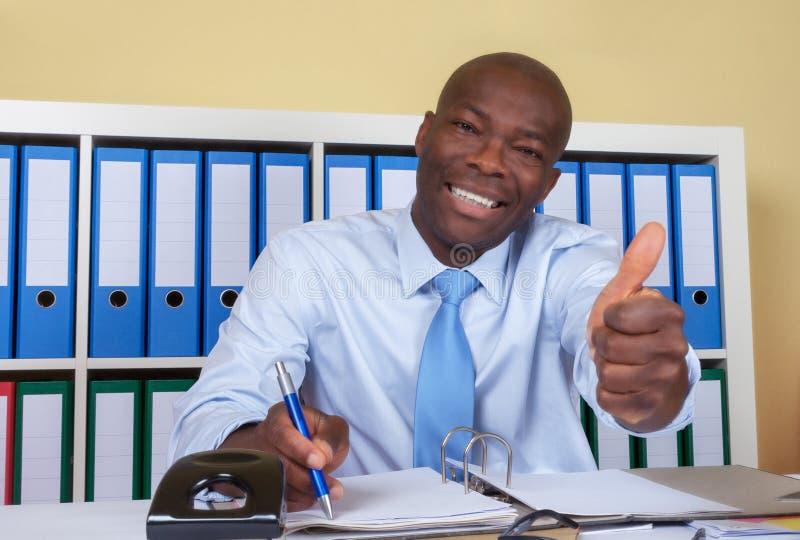 非洲商人在显示拇指的办公室 库存照片