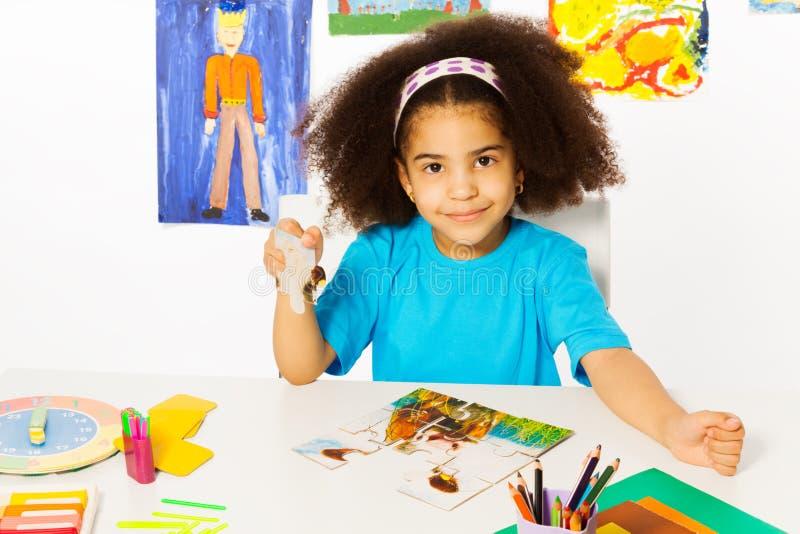 非洲女孩投入难题拼合在桌上 免版税库存照片