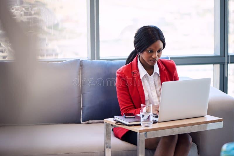 非洲女实业家繁忙工作在她的笔记本在企业休息室 免版税库存照片