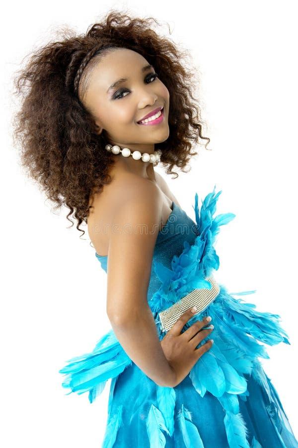 非洲女性模型佩带的绿松石用羽毛装饰的礼服,大蓬松卷发,斜向一边 库存照片
