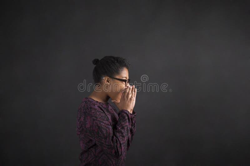 非洲妇女呼喊或尖叫在黑板背景 免版税库存图片