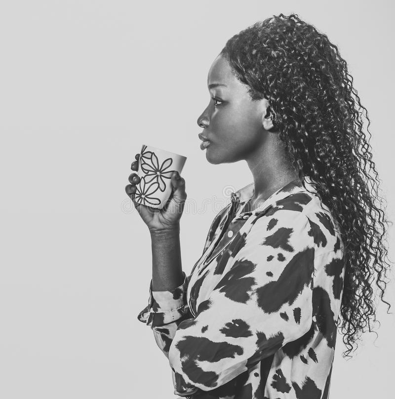 非洲妇女饮用的咖啡剪影 免版税图库摄影