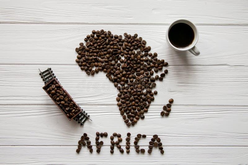 非洲的地图放置在与咖啡的白色木织地不很细背景的由烤咖啡豆制成,玩具火车 免版税库存图片