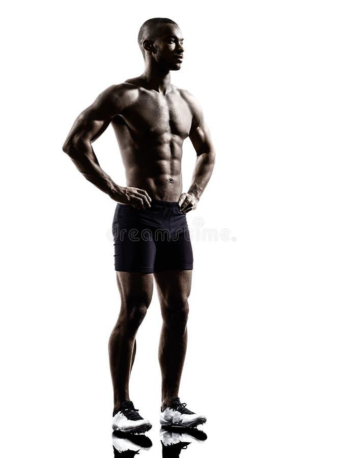 年轻非洲赤裸上身的肌肉修造人常设剪影 库存图片