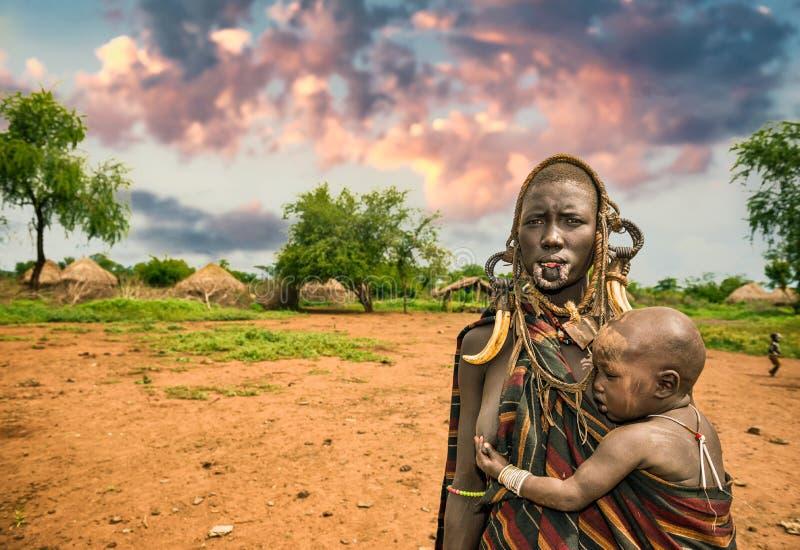 从非洲部落Mursi与她的婴孩,埃塞俄比亚的妇女 免版税库存图片
