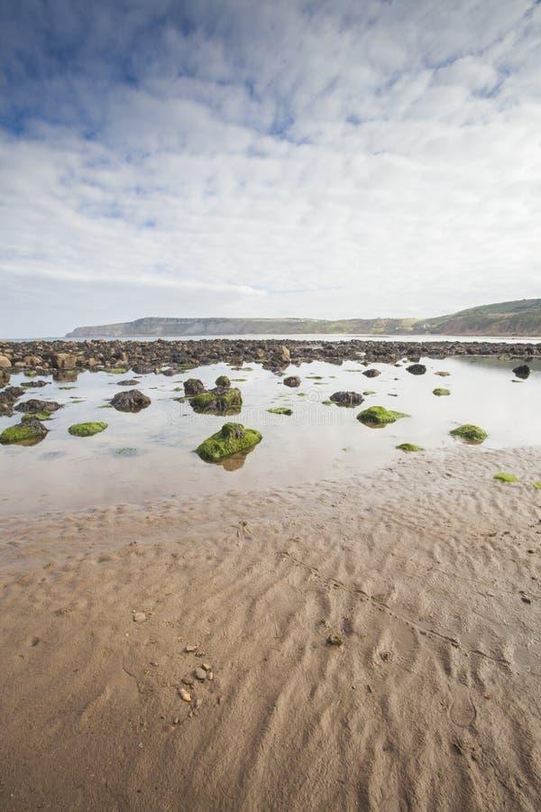 靠岸与在沙子的岩石在Cayton海湾,英国 免版税库存照片