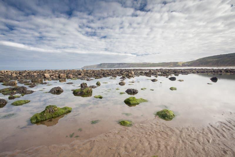 靠岸与在沙子的岩石在Cayton海湾,英国 库存图片
