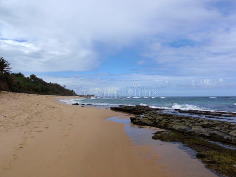 靠岸与在水和脚印刷品的岩石 免版税库存图片