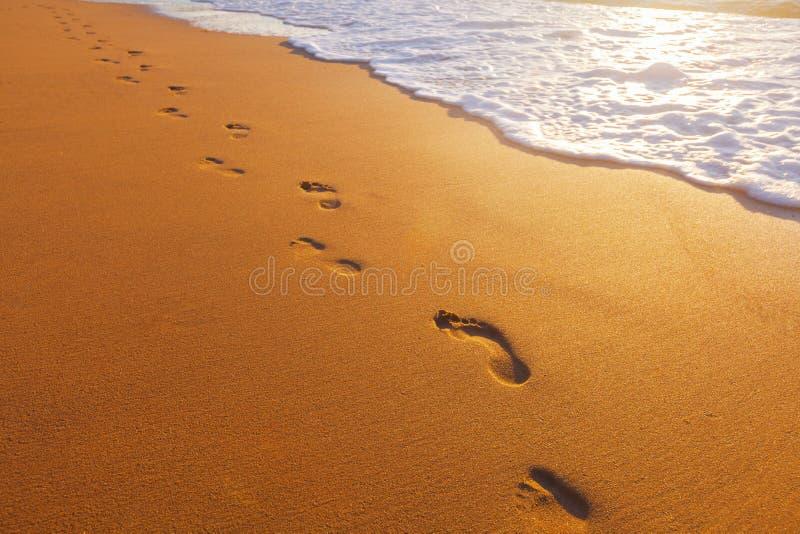 靠岸,波浪和脚步在日落时间 免版税库存图片
